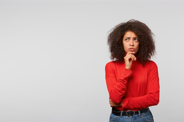 Premurosa e preoccupata giovane donna con acconciatura afro, guarda nell'angolo in alto a sinistra nello spazio vuoto della copia, tiene il pugno vicino al mento Foto Gratuite