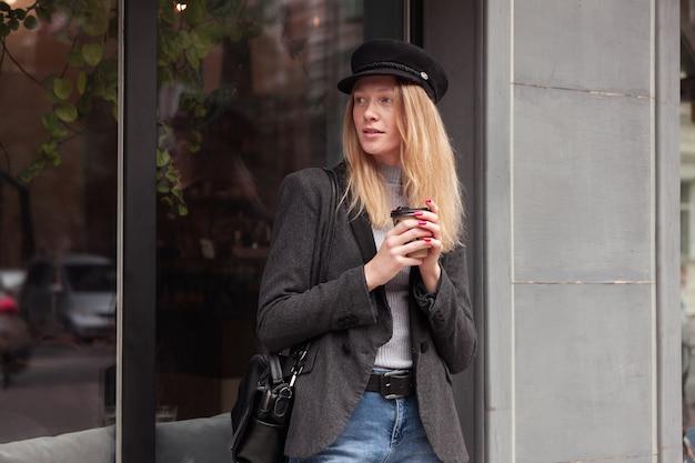 金髪の長い髪の思いやりのある若い魅力的な女性は、屋外を歩き、しんみりと脇を見て、黒いコートと帽子を着てコーヒーを飲みます 無料写真