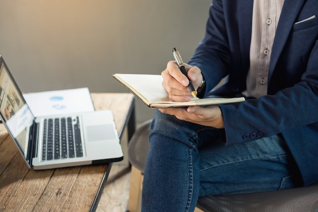 Thoughtful young business man in casual shirt holding note pad  in a notebook on a wooden table with pen working in a cafe Premium Photo
