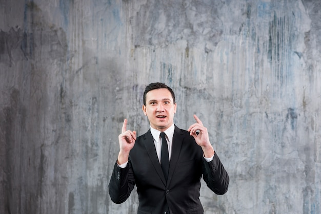 Thoughtful young businessman raising pointing fingers Free Photo