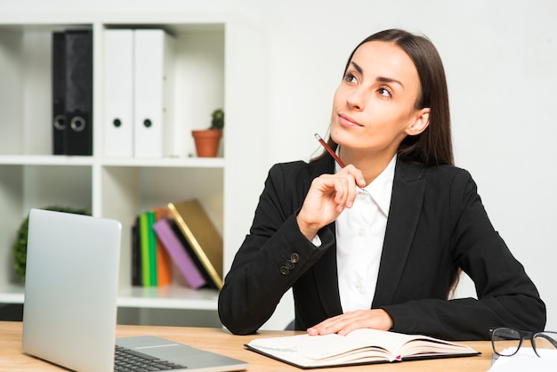 Thoughtful young businesswoman with diary and laptop on wooden desk in the office Free Photo