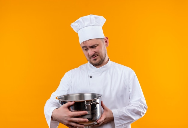 Thoughtful young handsome cook in chef uniform holding boiler and looking at it on isolated orange space Free Photo