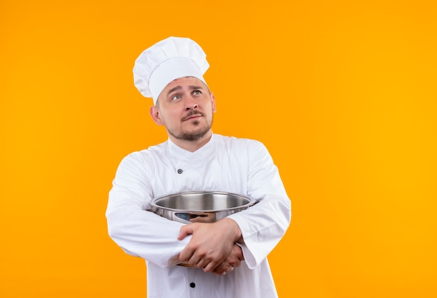 Thoughtful young handsome cook in chef uniform holding boiler looking up on isolated orange space Free Photo