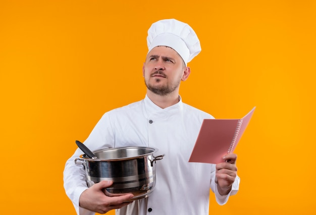 Thoughtful young handsome cook in chef uniform holding boiler and note pad looking up on isolated orange space Free Photo