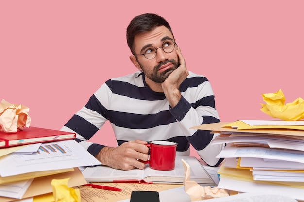 Thoughtful young man has contemplative expression, holds hand under chin, wears striped jumper, drinks fresh beverage, surrounded with pile of textbooks Free Photo