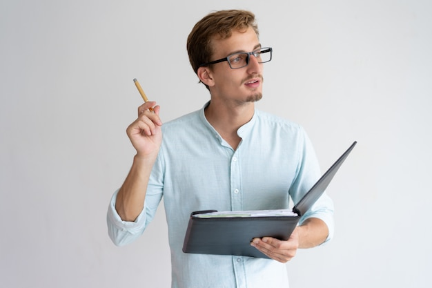Thoughtful young man holding file, pen and having idea Free Photo