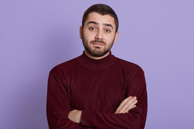 Giovane premuroso con sguardo scettico, dubbioso e diffidente in posa su sfondo lilla con le mani giunte, indossa un maglione bordeaux Foto Gratuite