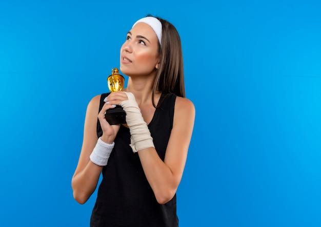 Premurosa giovane ragazza piuttosto sportiva che indossa la fascia e il braccialetto che tiene la tazza del vincitore con un polso ferito e avvolto con la benda che osserva in su isolato sullo spazio blu Foto Gratuite