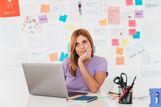 Thoughtful young redhead woman sitting at laptop against wall with notes Free Photo