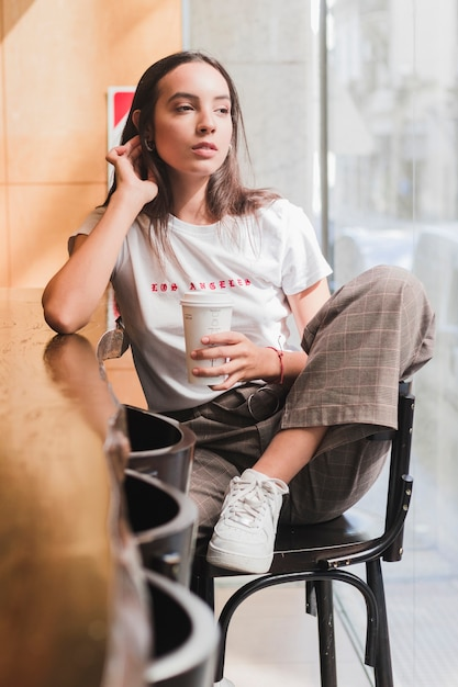 Thoughtful young woman sitting on chair in cafe holding the disposable coffee cup Free Photo
