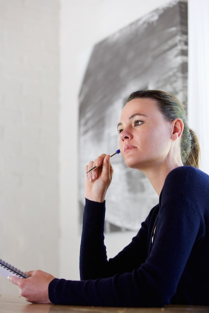Thoughtful young woman with pen and notepad Premium Photo