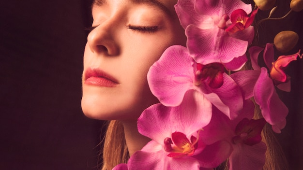 Thoughtful young woman with pink flower Free Photo