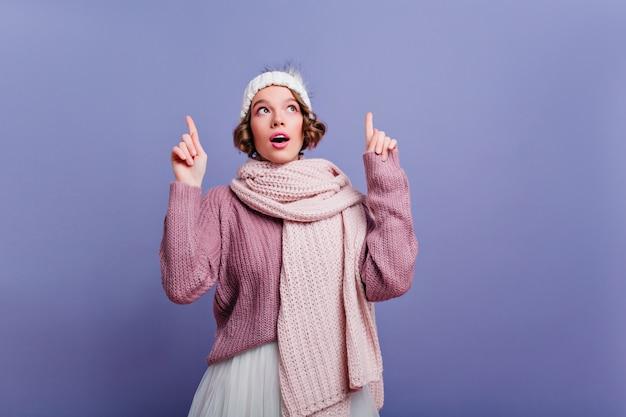 口を開けて見上げるかわいい帽子をかぶった思慮深く短い髪の少女。紫色の壁に冬のアクセサリーでポーズをとるのんきな女性モデル。 無料写真