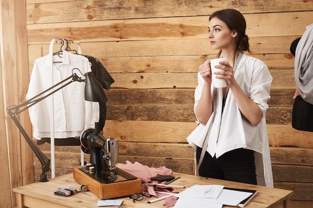 考えは私を運び去ります。ワークショップに立って、縫製をやめ、コーヒーを飲みながら、よそ見しながら考え、服の新しいデザインを計画している若いかわいい服デザイナー 無料写真