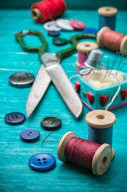 Thread buttons for crafts on turquoise wooden background. Premium Photo