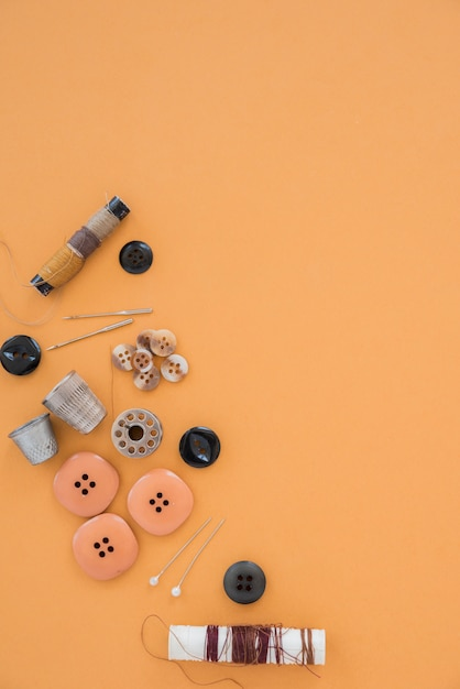 Thread spools; buttons; needle; thimble and button on an orange backdrop Free Photo