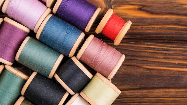 Thread spools on wood background Free Photo