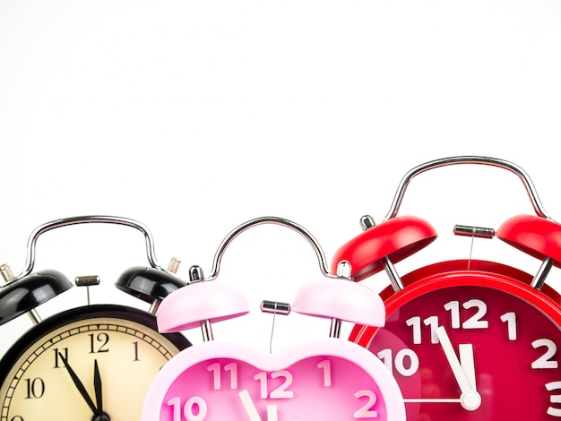 Three alarm clock, red, pink, black isolated on white background Premium Photo