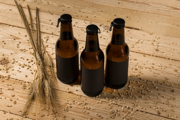 Three alcoholic bottles and ears of wheat on wooden surface Free Photo