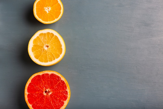 Three aligned citrusses on table with copy-space Free Photo