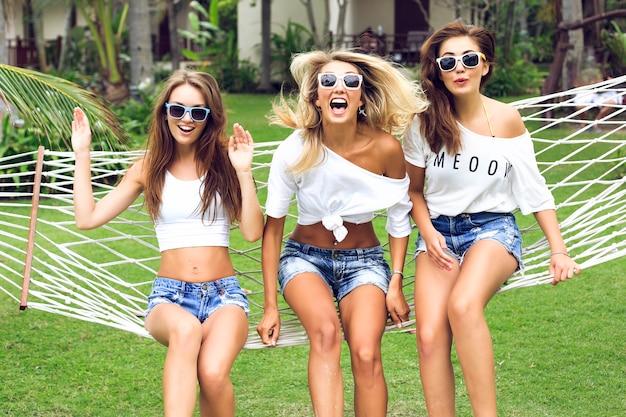 열대 정원에서 포즈를 취하고 트렌디 한 미니 반바지와 단순한 흰색상의를 입고 화려한 긴 섹시한 다리를 가진 세 명의 놀라운 멋진 여성 무료 사진
