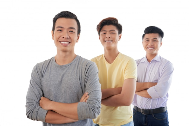 Three asian men standing in row with folded arms and smiling for camera Free Photo