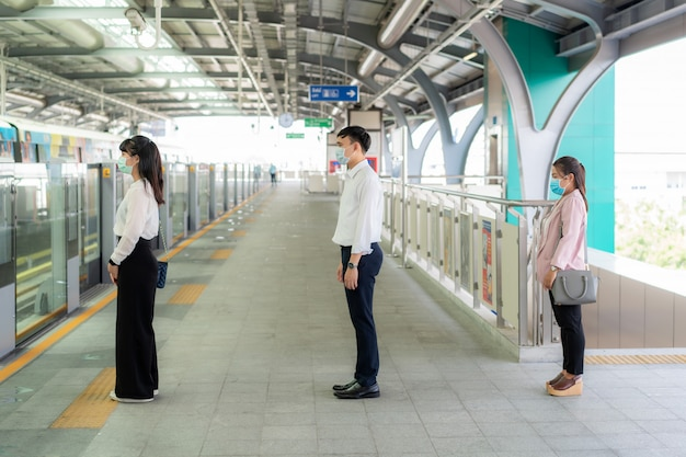 Three asian people wearing mask standing distance of 1 meter from other people keep distance protect from covid-19 viruses and people social distancing Premium Photo