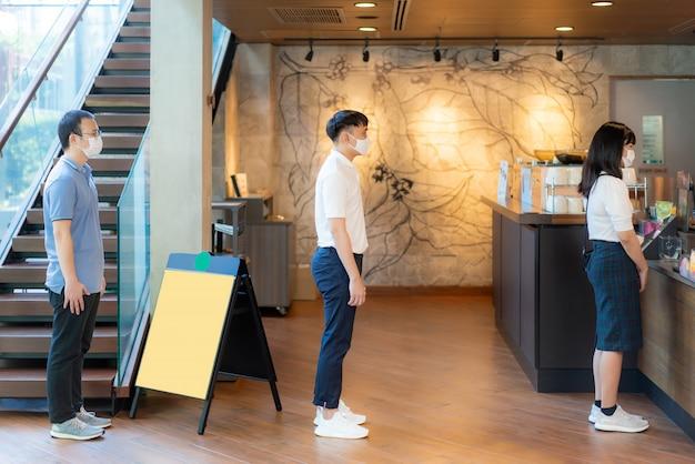 Три азиатских человека в маске, стоящие на расстоянии 6 футов от других людей, держатся на расстоянии от вирусов covid-19 и людей, которые дистанцируются от инфекций в кафе-кафе. Premium Фотографии