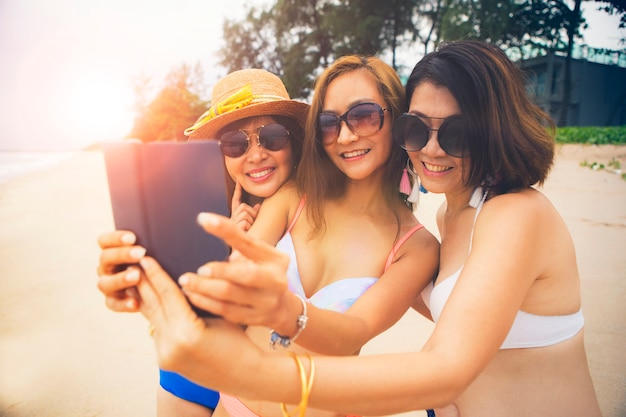Three asian woman relaxing on summer beach and taking selfie by smartphone Premium Photo