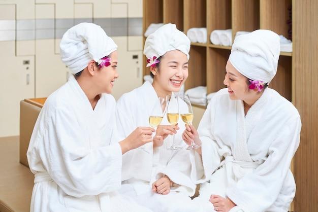 Три азиатских женщины пьют шампанское Premium Фотографии