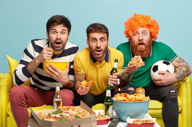 3人の驚いた男性の友人がカメラを見つめ、おいしいピザ、ポップコーン、ポテトチップスを食べ、冷たいビールを飲みます 無料写真