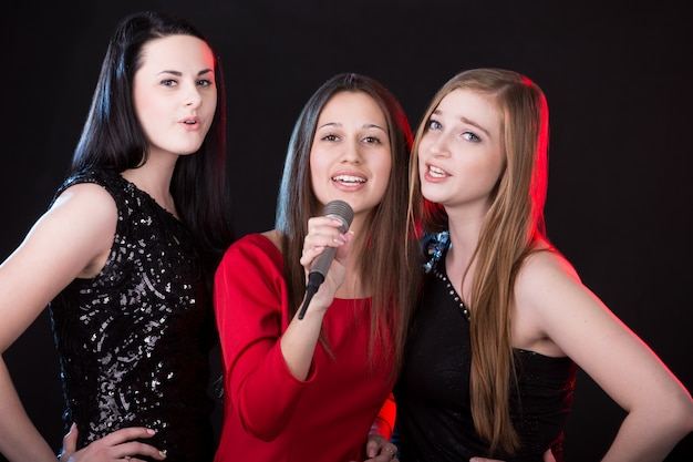 Three attractive young women singing Free Photo