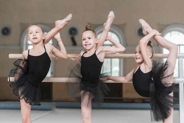 Three ballerina girls stretching their legs on barre in dance studio Free Photo