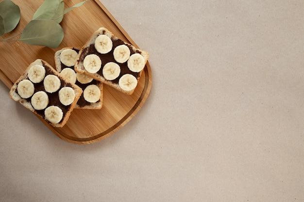 Three banana white bread toasts smeared with chocolate Premium Photo