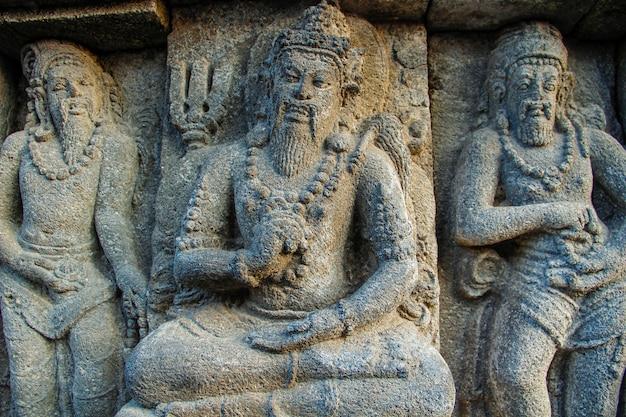 Три прекрасные фигуры в прамбанском храме. индонезия Premium Фотографии