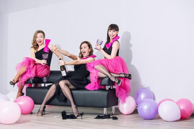 아름다운 메이크업 미소를 지닌 세 명의 아름다운 재미있는 트렌디 한 여성, 웃음과 풍선으로 축하 프리미엄 사진