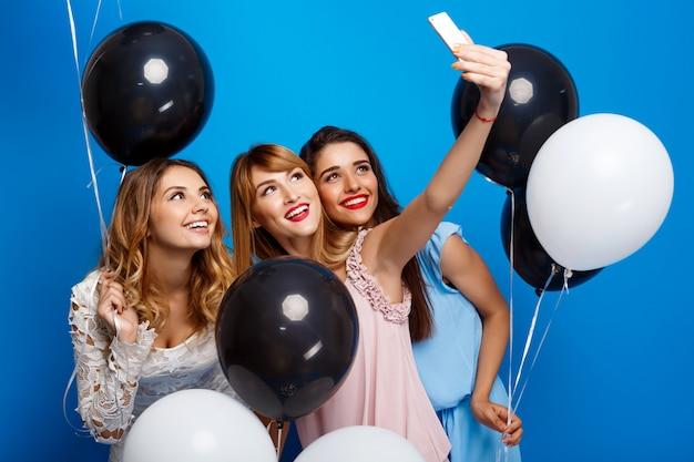 파란색 벽을 통해 파티에서 셀카를 만드는 세 아름다운 소녀 무료 사진