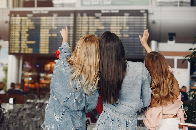Three beautiful girls standing by the airport Free Photo