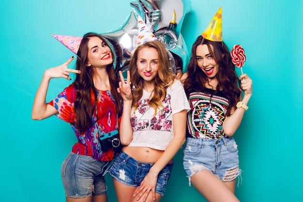 Три красивых счастливых женщины в стильном летнем наряде, бумажных шляпах и воздушных шарах чистоты, весело проводящих время и празднующих день рождения. красочный синий фон. красивая девушка держит большой леденец. Бесплатные Фотографии