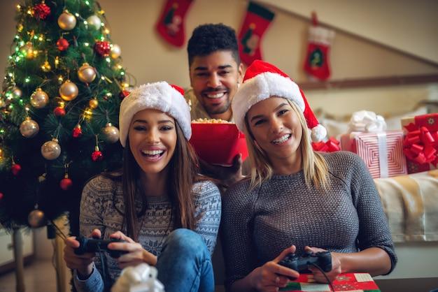 Три красивых игривых друга, наслаждающиеся видеоиграми и попкорном дома на рождественские праздники. Premium Фотографии