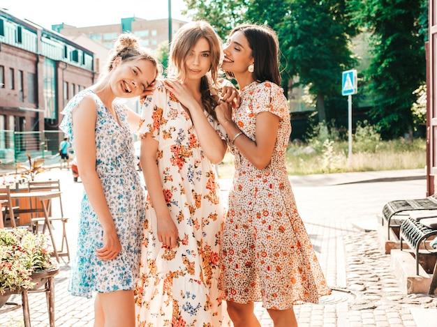 Три красивые улыбающиеся девушки в модном летнем сарафане позируют на улице Бесплатные Фотографии
