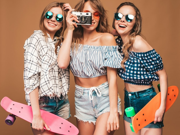 Three beautiful stylish smiling girls with colorful penny skateboards. women in summer checkered shirt clothes posing. taking pictures on retro photo camera Free Photo