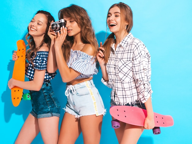 Three beautiful stylish smiling girls with colorful penny skateboards. women in summer checkered shirt clothes. taking pictures on retro photo camera Free Photo