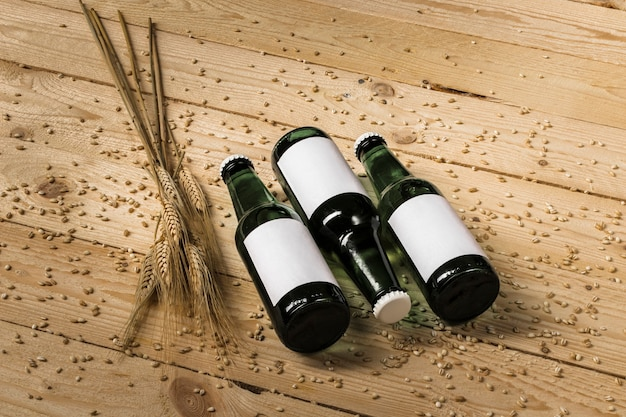 Three beer bottles and ears of wheat on wooden background Free Photo