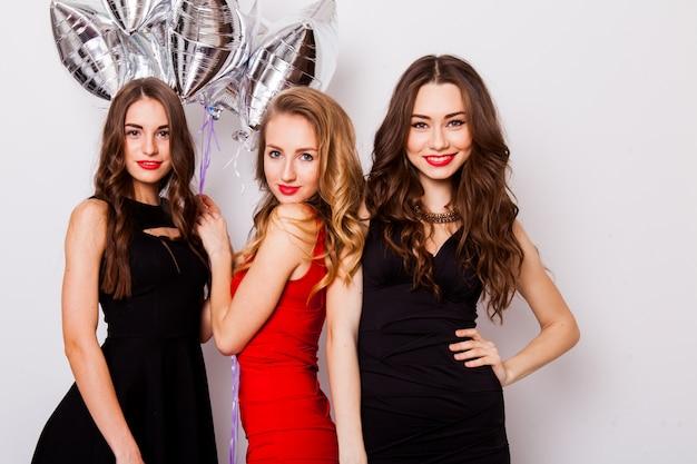 3人の親友がエレガントなイブニングドレスを着て屋内で誕生日を祝い、明るい化粧をしています。ハグし、手でサインを見せている女の子。 無料写真