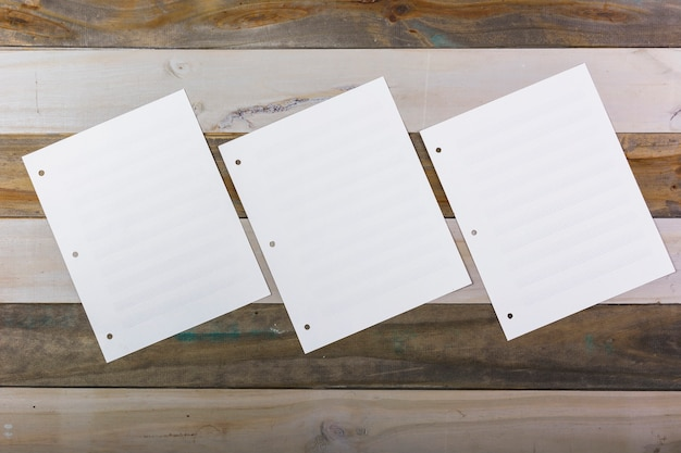 Three blank musical page attached on wooden wall Free Photo