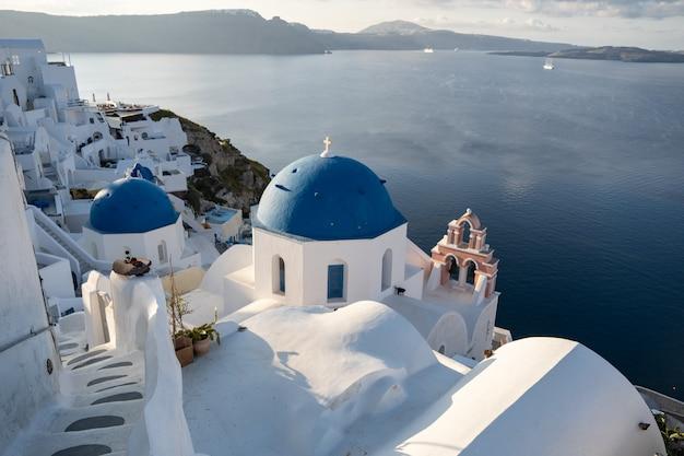 Three blue domes church santorini oia village in santorini island, greece. Premium Photo