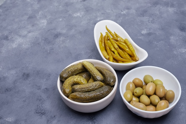 Three bowls of pickled cucumbers, peppers and olives on blue background. Free Photo