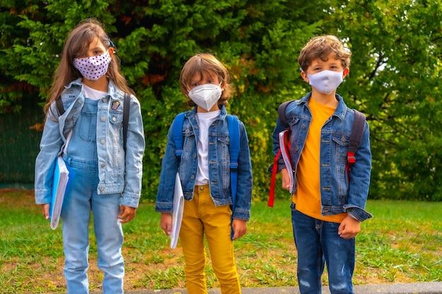 学校に戻る準備ができているフェイスマスクを持つ3人の兄弟。新しい正常性、社会的距離、コロナウイルスのパンデミック、covid-19。緑の植物を背景に学校へ行くのを待っています。 Premium写真