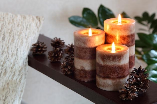 Three burning candles. home decor. living room decoration. Premium Photo